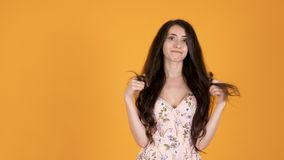 Mujer joven insatisfecha que juega con sus pelos largos almacen de video