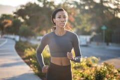 Mujer joven inspirada que corre en la luz del sol de oro en la ciudad Imagenes de archivo