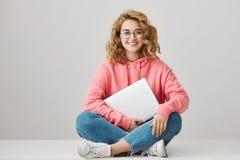 Mujer joven inteligente con el pelo rizado que se sienta en piso con las piernas cruzadas, gafas de moda que llevan y sudadera co Imágenes de archivo libres de regalías