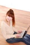 Mujer joven japonesa con el ordenador portátil en casa Imagen de archivo libre de regalías