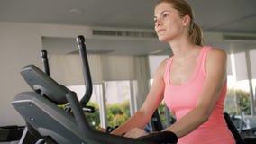 Mujer joven juguetona activa del ajuste hermoso que se resuelve en el gimnasio que hace ejercicios en un velosimulator metrajes