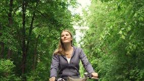 Mujer joven juguetona activa feliz de la cámara lenta en las sudaderas con capucha que completan un ciclo a través de parque sole metrajes
