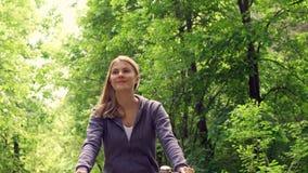 Mujer joven juguetona activa feliz de la cámara lenta en las sudaderas con capucha que completan un ciclo a través de parque sole almacen de metraje de vídeo