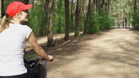 Mujer joven juguetona activa feliz en el casquillo rojo que completa un ciclo a través de parque soleado el día del ` s del veran metrajes