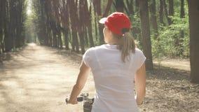 Mujer joven juguetona activa feliz en el casquillo rojo que completa un ciclo a través de parque soleado el día del ` s del veran almacen de metraje de vídeo