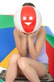 Mujer joven juguetona el día de fiesta que oculta detrás de una pelota de playa colorida Fotos de archivo libres de regalías