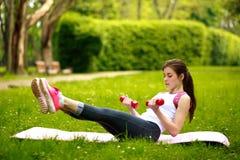 Mujer joven juguetona que estira con las pesas de gimnasia, haciendo aptitud Imágenes de archivo libres de regalías