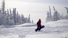 Mujer joven juguetona que lleva la snowboard pesada al pico de monta?a el vacaciones de invierno C?mara lenta 3840x2160, 4K metrajes