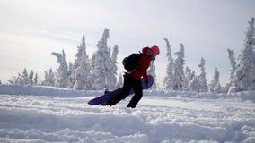 Mujer joven juguetona que lleva la snowboard pesada al pico de monta?a el vacaciones de invierno C?mara lenta 3840x2160 almacen de metraje de vídeo