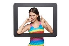 Mujer joven juguetona que mira a través de marco de la tableta Imagen de archivo