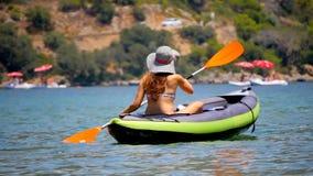 Mujer joven kayaking en el mar almacen de metraje de vídeo