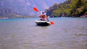 Mujer joven kayaking en el mar almacen de video