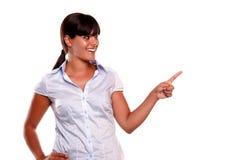 Mujer joven latina que mira y que señala su izquierda Foto de archivo libre de regalías