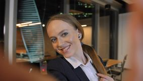 Mujer joven linda atractiva que toma el selfie en la oficina en ciudad grande metrajes