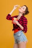 Mujer joven linda cómica graciosamente que se divierte con las patatas fritas Foto de archivo libre de regalías
