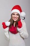 Mujer joven linda con el sombrero de Papá Noel que goza del café Imagen de archivo