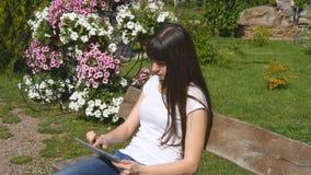 Mujer joven linda con la PC de la tableta que se sienta en banco en el parque de la ciudad Muchacha que mecanografía en la tablet almacen de video