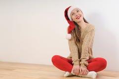 Mujer joven linda en el sombrero de santa que sueña con el regalo de la Navidad Imagen de archivo