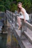 Mujer joven linda en el vestido blanco que se sienta en el lado del puente Imagen de archivo