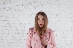 Mujer joven linda en la chaqueta de cuero Modelo de moda en chaqueta de cuero rosada Presentación cerca de la pared de ladrillo b foto de archivo