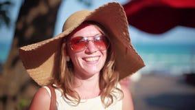 Mujer joven linda en sombrero y gafas de sol que sonríe mientras que ella está en una playa soleada 1920x1080 almacen de metraje de vídeo
