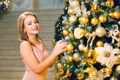 Mujer joven linda en un vestido de noche elegante rosado que permanece en un pasillo elegante y que viste para arriba un árbol de imagen de archivo