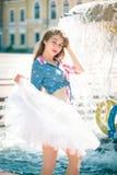 Mujer joven linda en una falda cerca de la fuente Imagen de archivo libre de regalías
