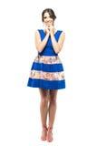 Mujer joven linda en vestido azul con la sonrisa perfecta que mira para arriba con la cabeza en manos Fotografía de archivo libre de regalías