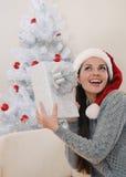 Mujer joven linda feliz de conseguir su presente para la Navidad Fotos de archivo libres de regalías