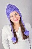 Mujer joven linda feliz que lleva el sombrero púrpura de la gorrita tejida Fotografía de archivo