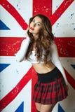 Mujer joven linda hermosa que presenta con la bandera BRITÁNICA en el backgr Fotos de archivo libres de regalías