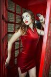 Mujer joven linda hermosa que presenta el teléfono rojo Cabine en Londres imagen de archivo