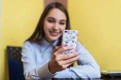 Mujer joven linda que charla con el amigo o que hace compras en línea con smartphone Cubierta hermosa del teléfono con las flores Fotos de archivo