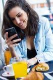 Mujer joven linda que charla con su smartphone Imagen de archivo libre de regalías