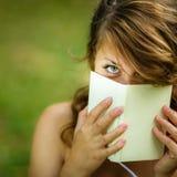 Mujer joven linda que cubre su cara con un libro Fotos de archivo