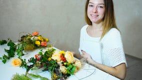 Mujer joven linda que detiene al florista con sonrisa y que presenta con la más gest Imagen de archivo libre de regalías