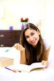 Mujer joven linda que estudia en cama en casa Fotografía de archivo