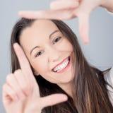 Mujer joven linda que hace el marco de la mano Fotografía de archivo libre de regalías