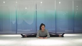 Mujer joven linda que hace estirar usando goma e inclinaciones de la aptitud el cuerpo en diversos lados en la estera en el gimna metrajes