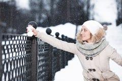 Mujer joven linda que juega con nieve en abrigo de pieles al aire libre Imagen de archivo libre de regalías