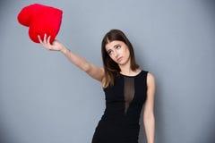 Mujer joven linda que lleva a cabo el corazón rojo Imagen de archivo libre de regalías