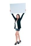 Mujer joven linda que lleva a cabo a la tarjeta en blanco fotos de archivo