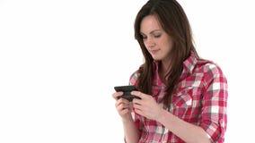 Mujer joven linda que manda un SMS en su teléfono móvil almacen de video