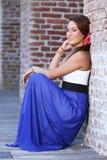 Mujer joven linda que se coloca cerca de una pared Fotos de archivo