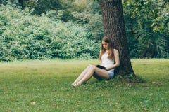 Mujer joven linda que se sienta en la hierba debajo de árbol y que lee el libro Fotos de archivo libres de regalías