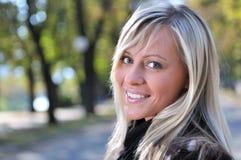Mujer joven linda rubia que sonríe al aire libre Imagenes de archivo