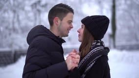 Mujer joven linda y hombre del retrato que se besan en parque del invierno debajo de nieve que cae El par feliz en amor disfruta  metrajes