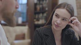 Mujer joven linda y un hombre rubio barbudo hermoso que se sienta en la tabla El hombre que cuenta una historia a su novia E almacen de video