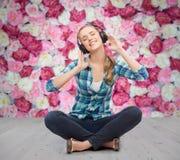 Mujer joven listeting a la música con los auriculares Foto de archivo