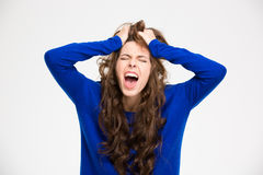 Mujer joven loca enojada con el pelo rizado largo que grita Imagen de archivo
